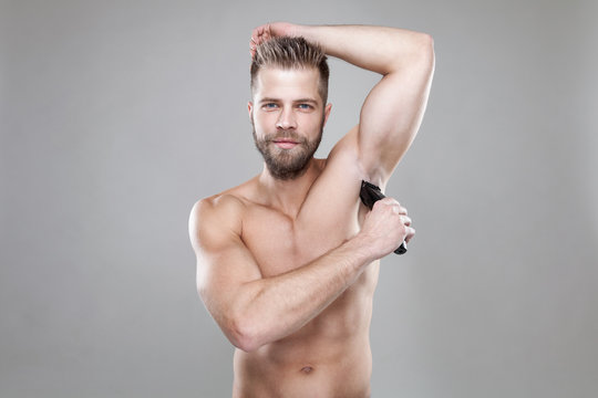 Handsome bearded man with a trimmer shaving off body hair