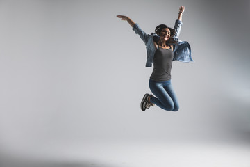 Playful young woman wearing casual jumping over grey background. Look at camera and screaming.
