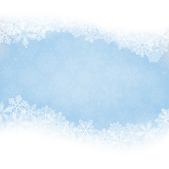 Winter background. Borders made of fluffy snowflakes with space for text on soft blue background with falling snow.