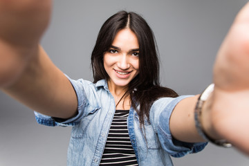 Young happy woman taking a selfie on a gray background