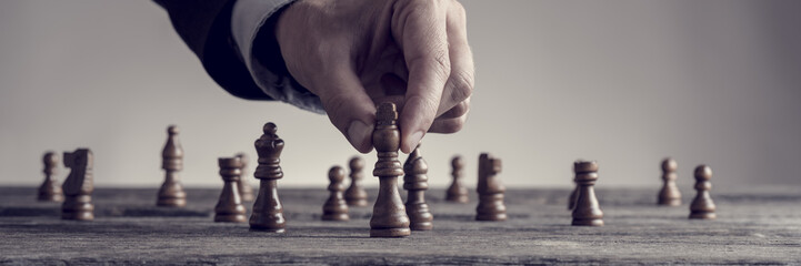 Wide cropped image of a human hand wearing business suit moving dark King chess piece
