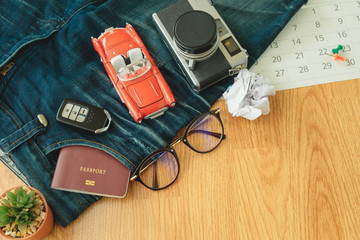 top view. passport book insert on pocket jean pants with glasses, plant in vase, camera, car and key placed on top. wooden are background. image for equipment, accessory, fashion, travel concept