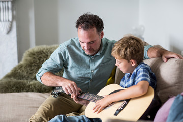 Father teaching son guitar chords