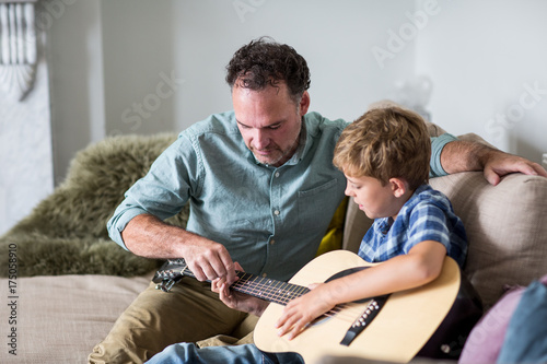 Father teaching son guitar chords\