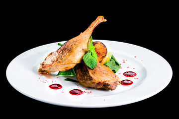 Juicy delicious cooked duck legs served with herbs and sauce in a white plate isolated on black background. Autumn menu in an Italian restaurant