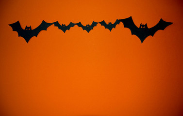 Silhouettes of bats. Swarm of bats on the orange background. Background for Halloween party. Flock of bats. Halloween decoration.
