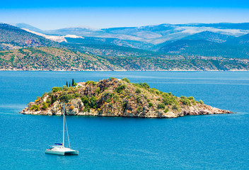 Tuinposter Eiland View of the sea on Tolo with a small island and a catamaran