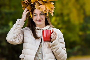 Female portrait in golden maple leaves  with red big tea cup in autumn outdoor