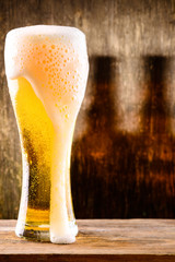 Glass of light beer on a wooden background with shadow of two bottles of beer