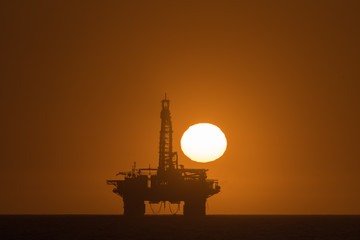 Sun setting over oil drilling platform at Longbeach in Namibia
