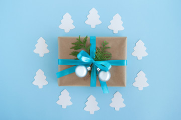 Gift box wrapped of craft paper, blue ribbon and decorated fir branches and silver Christmas balls on the blue background with paper fir tree, top view. Christmas present.