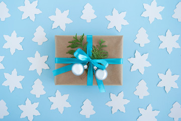 Gift box wrapped of craft paper, blue ribbon and decorated fir branches and silver Christmas balls on the blue background with white paper fir tree and star, top view. Christmas present.