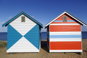 Two brightly painted beach huts on the iconic Brighton Beach in Melbourne