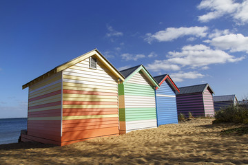 Colorful beach huts on Brighton Beach, Australia. Blue skies and ocean background.