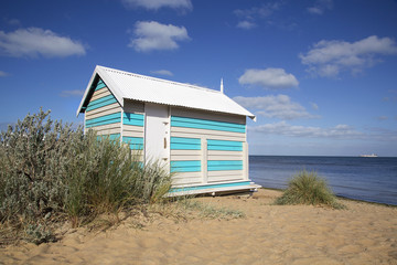 Beautiful beach hut on Melbourne's Brighton Beach with a summer blue sky and ocean background