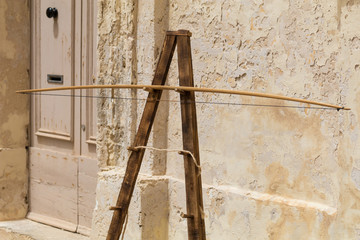 Traditional Medieval stand for archery practice bow in front of ancient wall, Medieval Mdina, Malta, April 2017