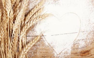 пшеница и мука лежат на деревянном столе