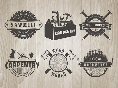 Woodwork logos. Vector badges for carpentry, sawmill, lumberjack service or woodwork shop. Set of hand tools labels on vintage wooden background.