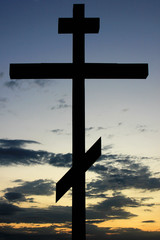 Silhouette of orthodox cross against sunset sky background