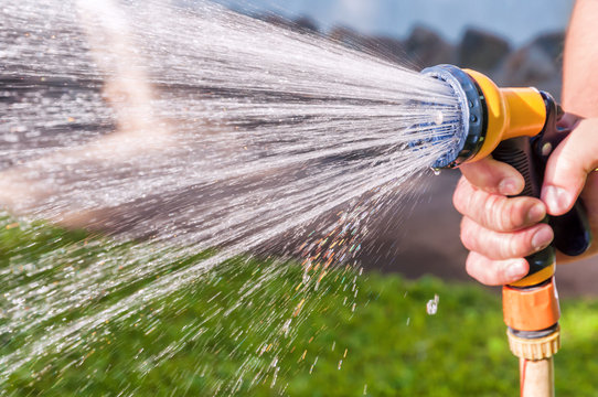 watering the grass with hose