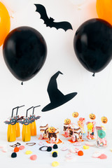 Halloween party decoration with candies and drinks on a white table.