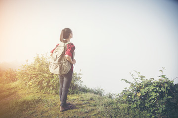 Hipster young girl with backpack enjoying sunset on peak of foggy mountain. Tourist traveler on background view mockup. Hiker looking sunlight in trip
