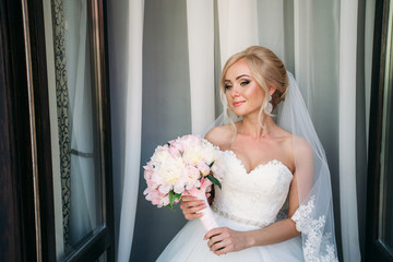Portrait of a bride in a wedding dress. The bride dresses in the hotel.