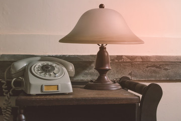 Vintage - old gray phone and retro lamp on the desk - 80's concept image