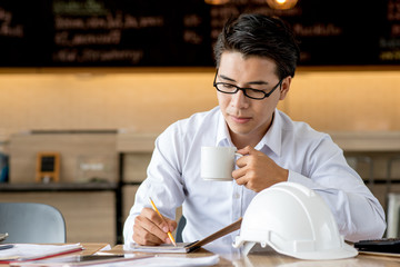 Business man working with documents and writing something idea on blank notebook in cafe