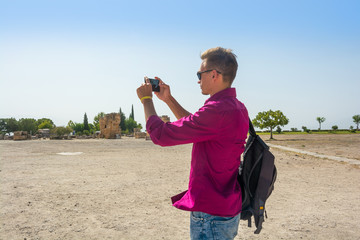 Young guy with backpack, tourist, takes pictures with his mobile phone view of the ruins of the city of Hierapolis, modern name of the location - Pamukkale, Turkey.