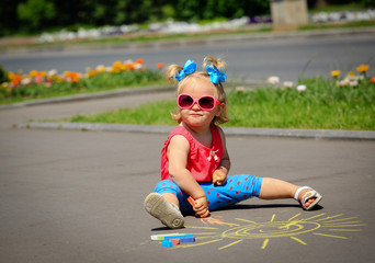 cute little girl drawing sun on a street