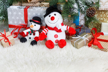 Cozy christmas background. Toy snowmen and presents under new year tree
