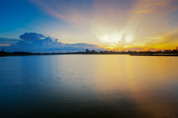 Beautiful sunset landscape with blue sky over lake