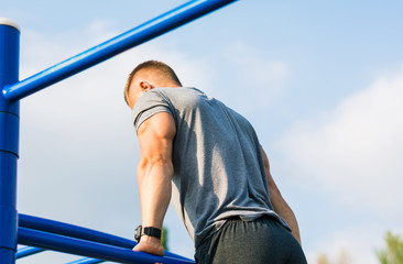 Man performing Russian pull ups on a workout outdoors