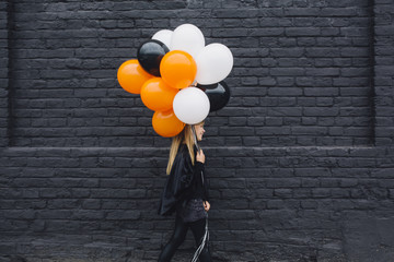 Blonde Girl in a Witch Halloween Costume Holding Balloons