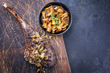 Barbecue dry aged wagyu tomahawk steak with roast onion and chanterelle as top view on old wooden board