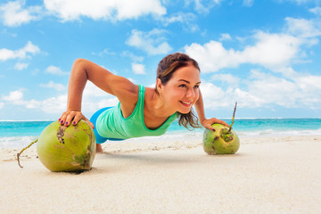Active woman doing fitness exercise plank on coconut to keep fit and health. Beach surf background. Healthy lifestyle, morning workout, sport activity on summer family vacation in tropical island.