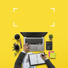 Office workplace with laptop, notebook, hand, office supplies, on yellow background. Solution,...