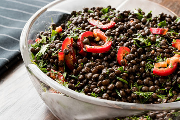 Black Lentil Salad with Red Peppers and Parsley in glass bowl.