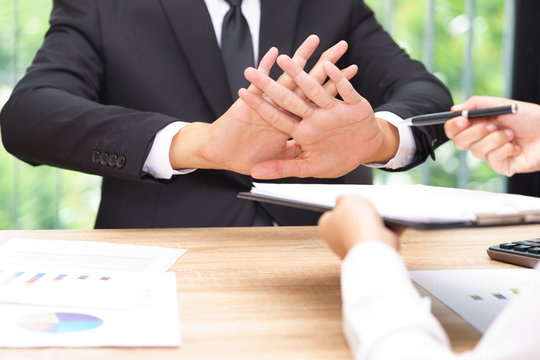Businessman says no or hold on when businesswoman giving pen for signing a contract