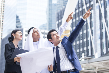Businesspeople with Arab man Pointing to City for Work. People and Arab working concept. Arab man holding Blueprint and Thinking about Work.
