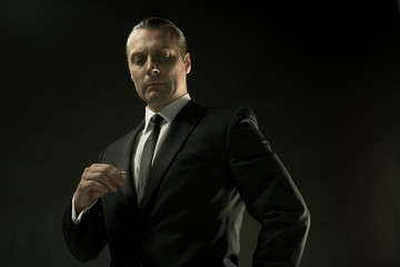 The attractive man in black suit on dark background