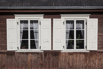 Two windows in a traditional wooden house in rural Lithuania