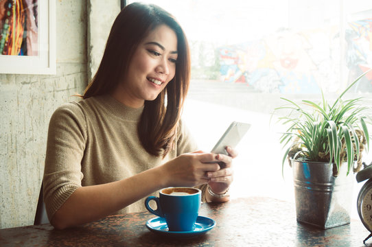 Asian woman shopping online with credit card payment in coffee shop feeling happy smile