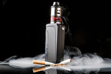 Tobacco cigarette crushed under electronic cigarette with smoke cloud