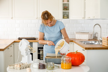 Woman in kitchen with pumpkins
