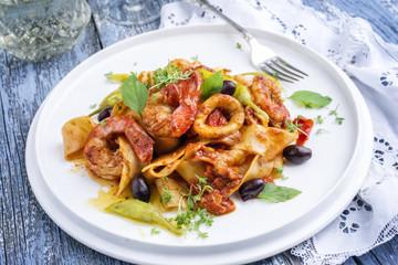Italian tagliatelle con gamberi e calamari in salsa di pomodoro with olives and peperoni as close-up on a plate