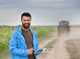 Farmer holding tablet with tractor behind