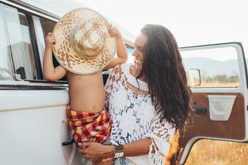 Young Smiling Brunette Holding Cute Young Boy Hiding Behind Straw Hat