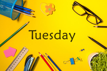 TUESDAY. Office supplies or student outfit on yellow table. Business creative consept, top view